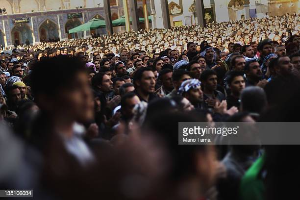 Shi'ite worshipers look on during an Ashura commemoration ceremony inside Kadhimiya shrine on December 6 2011 in Baghdad Iraq Ashura marks the death...