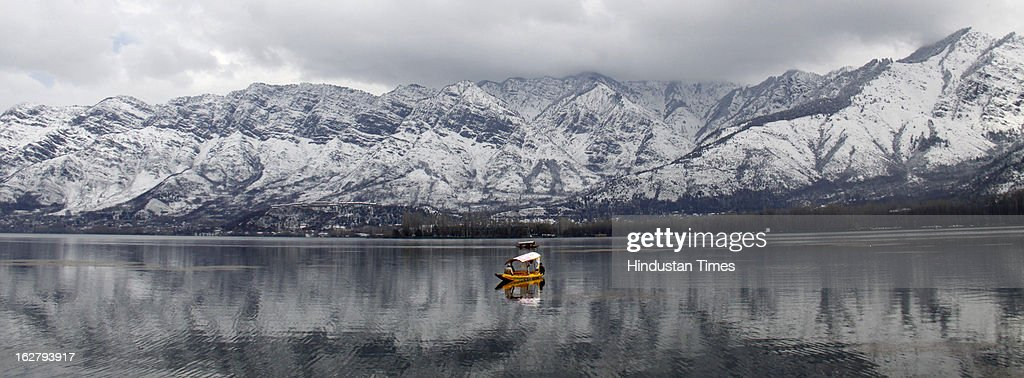 A Shikara crosses the Dal Lake with the backdrop of snow coverd mountain, on February 27, 2013 in Srinagar, India. Kashmir valley was hit by a fresh spell of rains and snow during the preceding night of February 26 and 27.