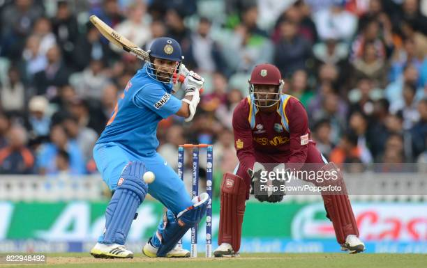 Shikhar Dhawan batting for india during his innings of 102 not out watched by West Indies wicketkeeper Johnson Charles in the ICC Champions Trophy...