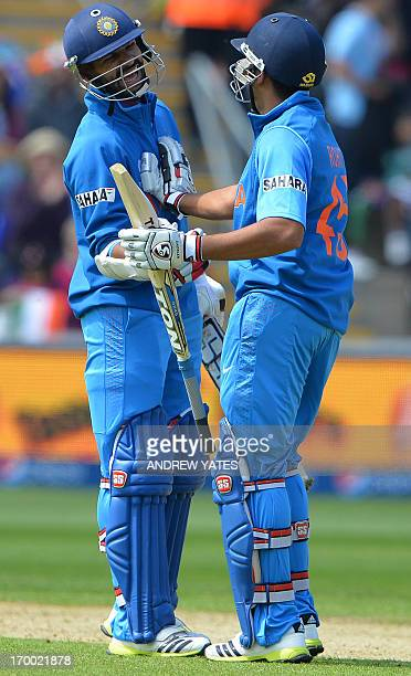 Shikhar Dhawan congratulates India's Rohit Sharma after Sharma reached his half century during the 2013 ICC Champions Trophy cricket match between...