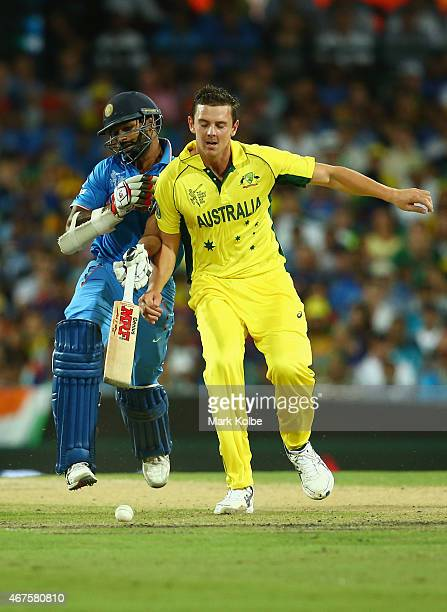 Shikhar Dhawan of India and Josh Hazlewood of Australia collisde midpitch during the 2015 Cricket World Cup Semi Final match between Australia and...