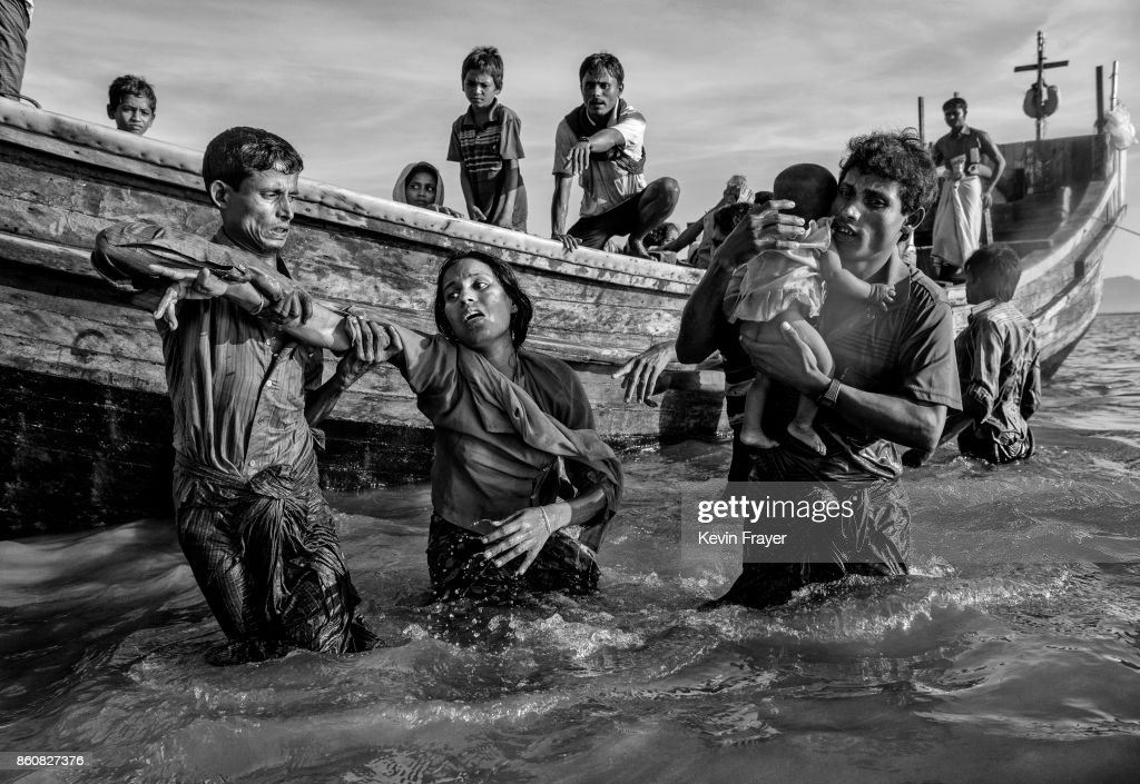 COX'S BAZAR, BANGLADESH - OCTOBER 01: A Rohingya refugee woman is helped from a boat as she arrives exhausted on the Bangladesh side of the Naf River at Shah Porir Dwip after fleeing her village in Myanmar, on October 1, 2017 in Cox's Bazar, Bangladesh. More than half a million Rohingya refugees have flooded into Bangladesh to flee an offensive by Myanmar's military that the United Nations has called 'a textbook example of ethnic cleansing'. The refugee population is expected to swell further, with thousands more Rohingya Muslims said to be making the perilous journey on foot toward the border, or paying smugglers to take them across by water in wooden boats. Hundreds are known to have died trying to escape, and survivors arrive with horrifying accounts of villages burned, women raped, and scores killed in the 'clearance operations' by Myanmar's army and Buddhist mobs that were sparked by militant attacks on security posts in Rakhine state on August 25, 2017. What the Rohingya refugees flee to is a different kind of suffering in sprawling makeshift camps rife with fears of malnutrition, cholera, and other diseases. Aid organizations are struggling to keep pace with the scale of need and the staggering number of them - an estimated 60 percent - who are children arriving alone. Bangladesh, whose acceptance of the refugees has been praised by humanitarian officials for saving lives, has urged the creation of an internationally-recognized 'safe zone' where refugees can return, though Rohingya Muslims have long been persecuted in predominantly Buddhist Myanmar. World leaders are still debating how to confront the country and its de facto leader, Aung San Suu Kyi, a Nobel Peace Prize laureate who championed democracy, but now appears unable or unwilling to stop the army's brutal crackdown.