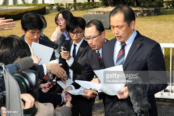 Shikoku Electric Power Co staffs read statement after a request for a temporary injunction on the Ikata nuclear plant had been rejected in front of...