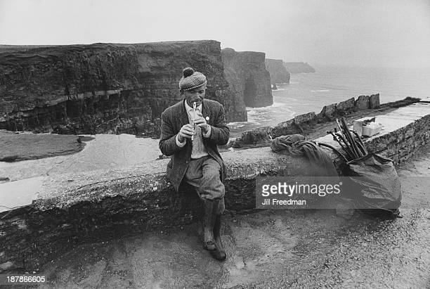 Shillelagh salesman Denny plays his penny whistle at the cliffs of Moher County Cavan Ireland 1974