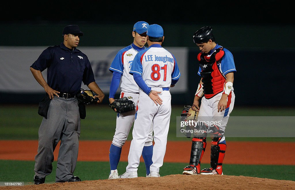 Shim Jae-Min of South Korea talks with South Korean team namager Lee Jeong-Hoon in the seventh inning during the 18U Baseball World Championship match between Japan and South Korea at Mokdong Stadium on September 6, 2012 in Seoul, South Korea.