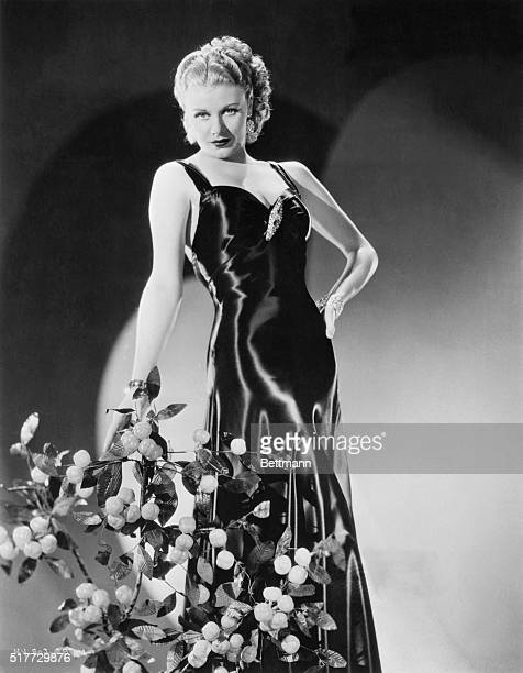 Shimmering black satin is used in the creation of this stunning evening gown worn by the scintillating Ginger Rogers RKORadio star Molding the form...