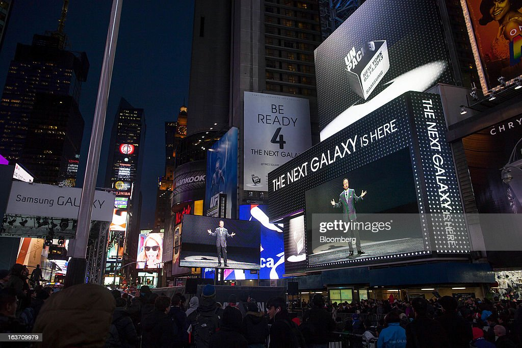 J.K. Shin, head of Samsung Electronics Co.'s mobile division, is displayed on screens as spectators gather at the release of the Samsung Electronics Co. Galaxy S4 smartphone in Times Square in New York, U.S., on Thursday, March 14, 2013. Samsung Electronics Co. unveiled the Galaxy S4 with a bigger screen and software that tracks eye movements as the world's biggest smartphone seller takes its battle with Apple Inc. to the iPhone maker's home market. Photographer: Michael Nagle/Bloomberg via Getty Images