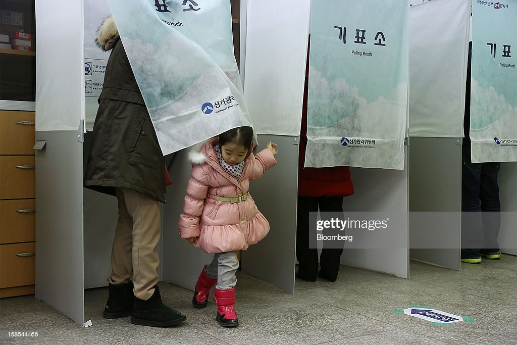 Shin Hee Yeon, 5, exits a voting booth while her mother fills out her ballot for the presidential election at a polling station in Seoul, South Korea, on Wednesday, Dec. 19, 2012. South Koreans go to the polls today to choose either a dictator's daughter or a one-time dissident as president, both of whom pledge to reverse slowing growth, a widening income gap and deteriorating North Korea ties. Photographer: SeongJoon Cho/Bloomberg via Getty Images