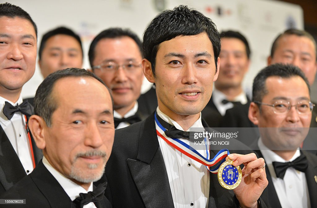 Shin Miyazaki of Japan (C) holds up his winner's medal as he celebrates his win during an awards ceremony of the International Georges Baptiste Cup world service competition in Tokyo on November 9, 2012. Miyazaki took first place in the competition. AFP PHOTO / KAZUHIRO NOGI