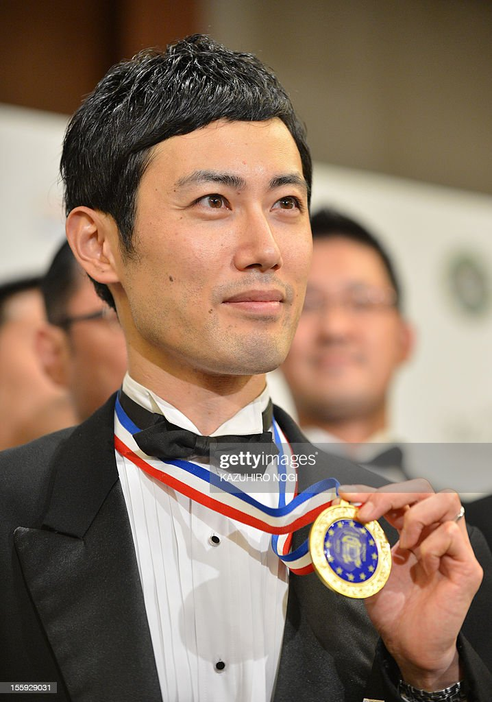 Shin Miyazaki of Japan holds up his winner's medal as he celebrates his win during an awards ceremony of the International Georges Baptiste Cup world service competition in Tokyo on November 9, 2012. Miyazaki took first place in the competition.