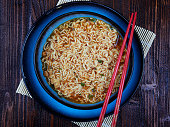 Shin Ramyun noodles, prepared, in a blue bowl set on a brown wooden board, with red chopsticks, top view