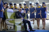 Shinichi Nishikubo president of Skymark Airlines Inc poses for a photograph with members of the company's cabin crew at a hangar during a media...
