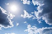 Shining Sun framed by clouds on a blue sky