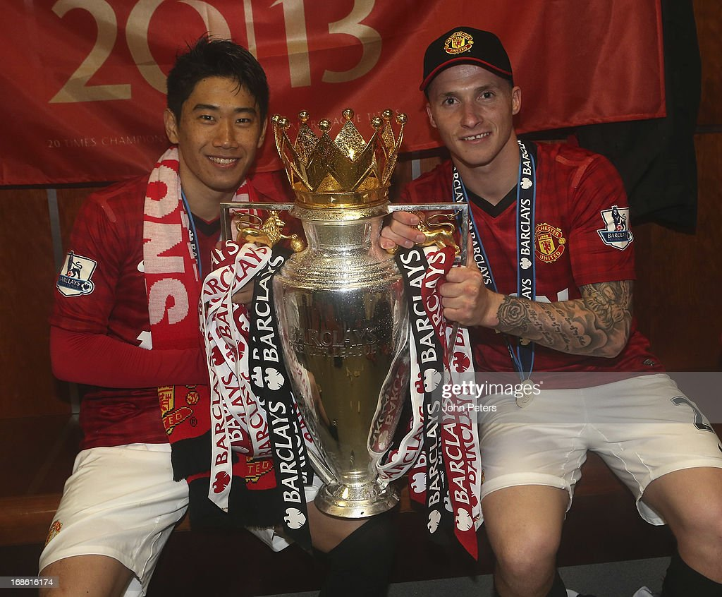 Shinji Kagawa and Alexander Buttner of Manchester United celebrate with the Barclays Premier League trophy in the dressing room after the Barclays Premier League match between Manchester United and Swansea at Old Trafford on May 12, 2013 in Manchester, England.