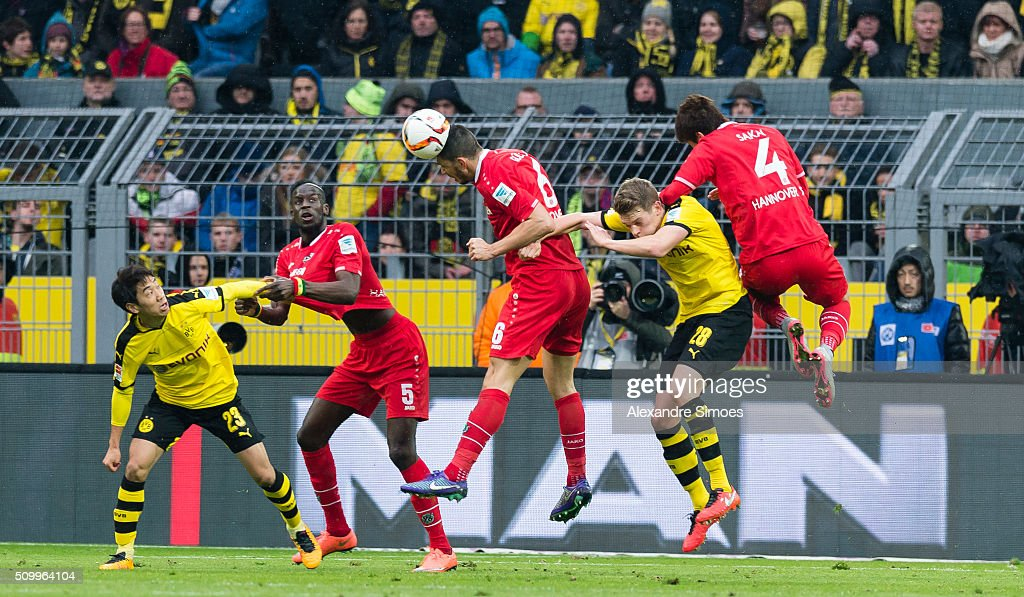 Shinji Kagawa and Matthias Ginter of Borussia Dortmund challenge Salif Sane, Ceyhun Guelselam and Hiroki Sakai of Hannover in an aerial duel during the Bundesliga match between Borussia Dortmund and Hannover 96 at Signal Iduna Park on February 13, 2016 in Dortmund, Germany.