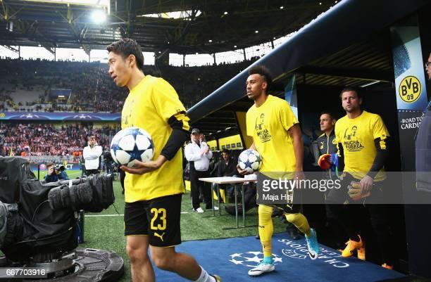 Shinji Kagawa and PierreEmerick Aubameyang of Borussia Dortmund walk out wearing shirts for Marc Bartra who was injured in the team coach attack...