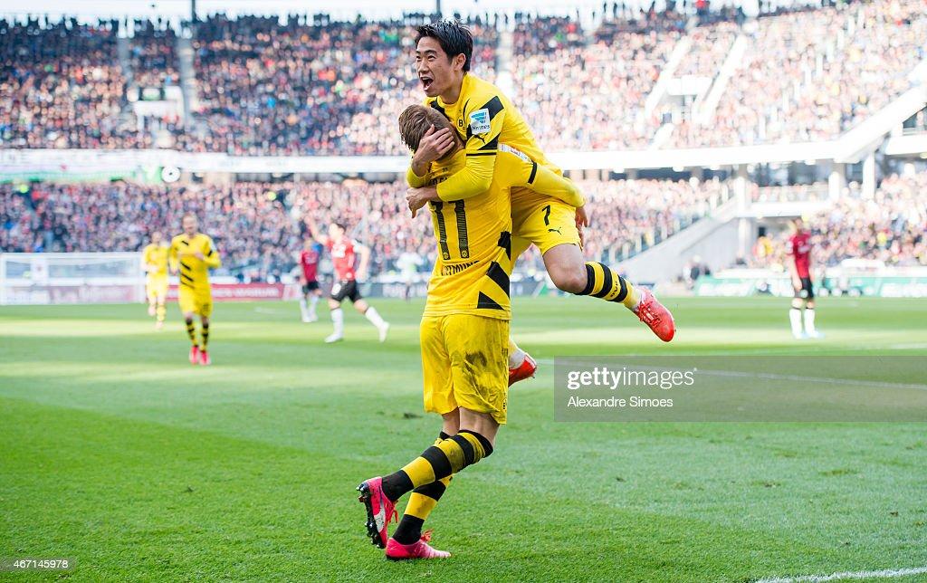 Shinji Kagawa of Borussia Dortmund celebrates scoring the goal to the 12 together with his team mate Marco Reus during the Bundesliga match between...