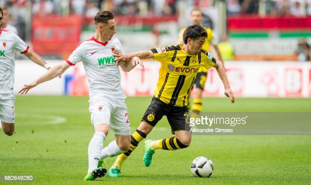 Shinji Kagawa of Borussia Dortmund challenges Dominik Kohr of FC Augsburg during the Bundesliga match between FC Augsburg and Borussia Dortmund at...
