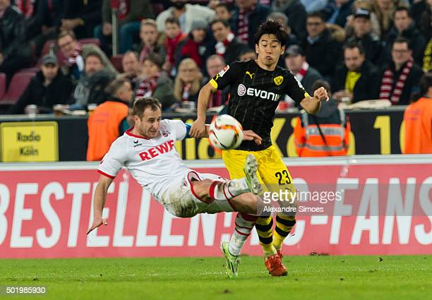 Shinji Kagawa of Borussia Dortmund gets challenged by Matthias Lehmann of Koln during the Bundesliga match between 1 FC Koeln and Borussia Dortmund...