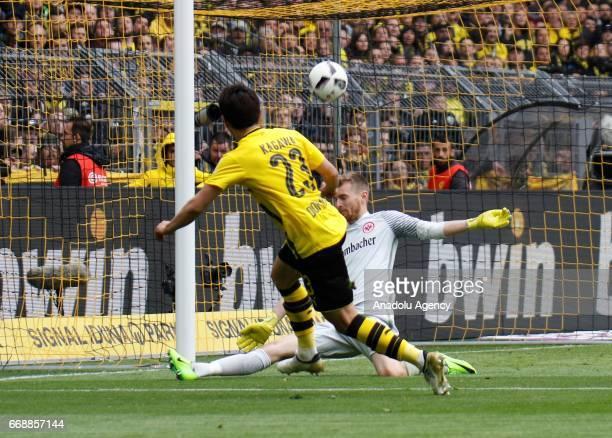 Shinji Kagawa of Borussia Dortmund in action with Lukas Hradecky of Eintrach Frankfurt during the Bundesliga soccer match between Borussia Dortmund...