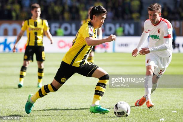 Shinji Kagawa of Borussia Dortmund is challenged by Daniel Baier of Augsburg during the Bundesliga match between FC Augsburg and Borussia Dortmund at...