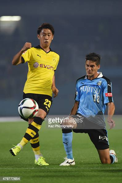 Shinji Kagawa of Borussia Dortmund passes the ball under the pressure from Elsinho of Kawasaki Frontale during the preseason friendly match between...