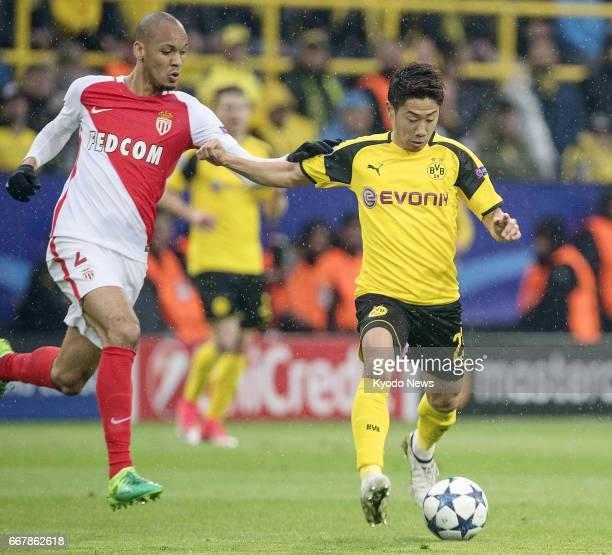 Shinji Kagawa of Borussia Dortmund tries to hold off Fabio Henrique Fabinho of AS Monaco during the first half of a Champions League quarterfinal...