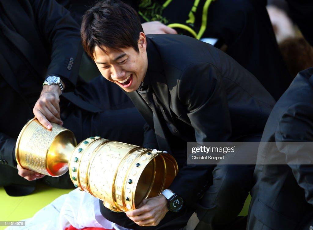 Shinji Kagawa of Dortmund catches the trophy during a parade at Borsigplatz celebrating Borussia Dortmund's Bundesliga and DFB Cup win on May 13 2012...