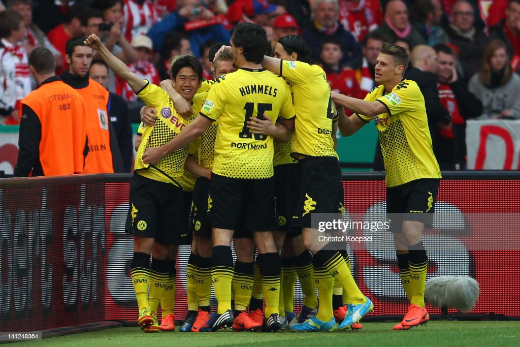 Shinji Kagawa of Dortmund celebrates the first goal with Mats Hummels Neven Subotic and Lukasz Piszczek during the DFB Cup final match between...