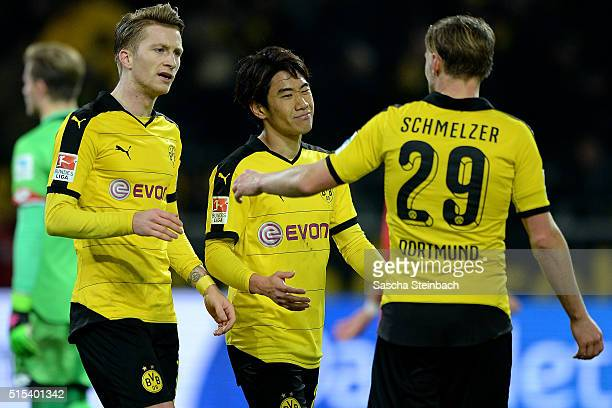 Shinji Kagawa of Dortmund celebrates with Marco Reus and Marcel Schmelzer after scoring his team's second goal during the Bundesliga match between...