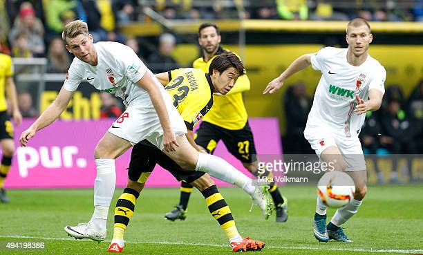 Shinji Kagawa of Dortmund challenges JanIngwer CallsenBracker of Augsburg during the Bundesliga match between Borussia Dortmund and FC Augsburg at...