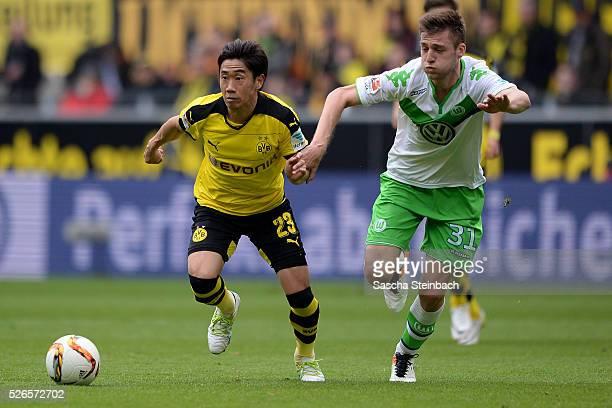 Shinji Kagawa of Dortmund goes past Robin Knoche of Wolfsburg during the Bundesliga match between Borussia Dortmund and VfL Wolfsburg at Signal Iduna...