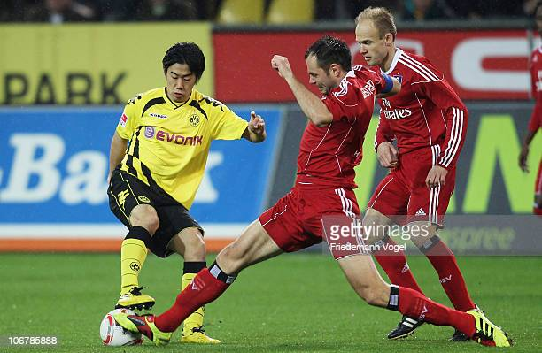 Shinji Kagawa of Dortmund Heiko Westermann and David Jarolim of Hamburg battle for the ball during the Bundesliga match between Borussia Dortmund and...