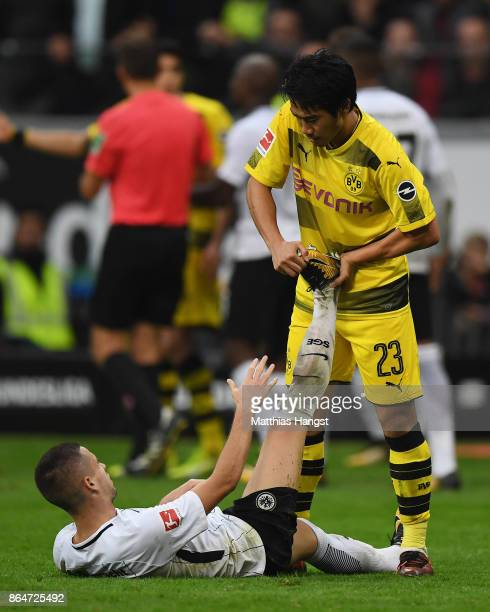 Shinji Kagawa of Dortmund helps Mijat Gacinovic of Frankfurt during the Bundesliga match between Eintracht Frankfurt and Borussia Dortmund at...