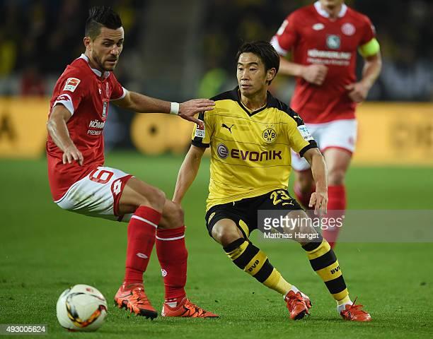 Shinji Kagawa of Dortmund is challenged by Danny Latza of Mainz during the Bundesliga match between Eintracht Frankfurt and Borussia Moenchengladbach...