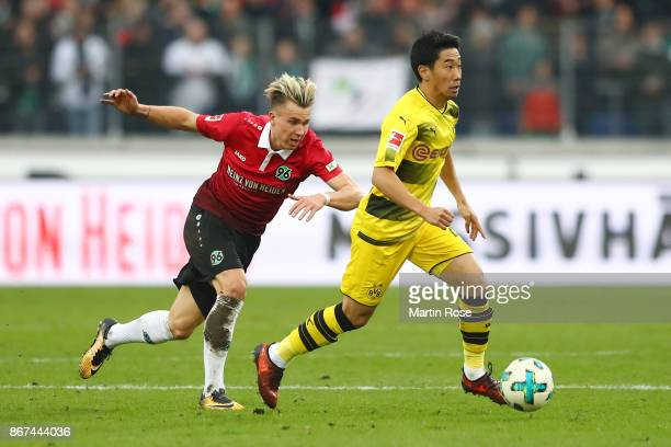Shinji Kagawa of Dortmund is chased by Felix Klaus of Hannover during the Bundesliga match between Hannover 96 and Borussia Dortmund at HDIArena on...