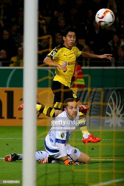 Shinji Kagawa of Dortmund scores the third goal against Lukas Kruse of Paderborn during the DFB Cup match between Borussia Dortmund and SC Paderborn...
