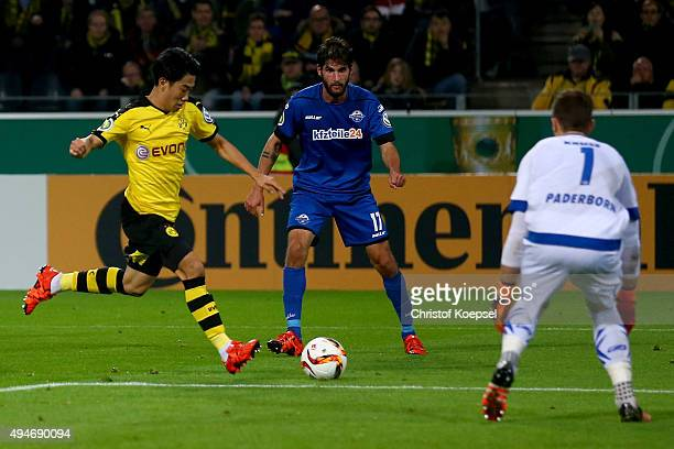 Shinji Kagawa of Dortmund scores the third goal against Lukas Kruse of Paderborn and Niklas Hoheneder of Paderborn during the DFB Cup match between...