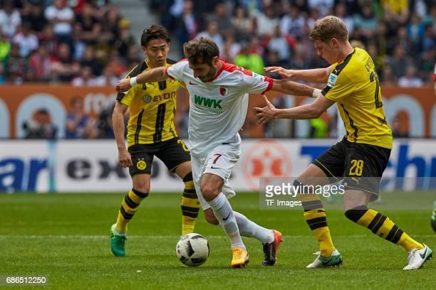 Shinji Kagawa of Dortmund und Matthias Ginter of Dortmund and Halil Altintop of Augsburg battle for the ball during the Bundesliga match between FC...