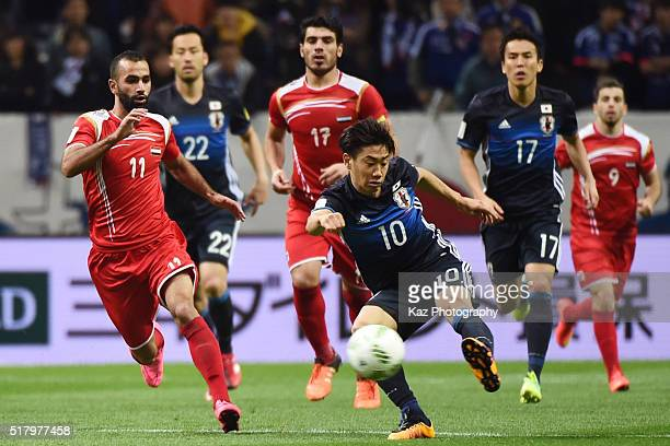 Shinji Kagawa of Japan and Osama Omari of Syria compete for the ball during the FIFA World Cup Russia Asian Qualifier second round match between...