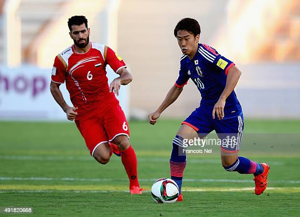 Shinji Kagawa of Japan compete for the ball with Zahir Algunami of Syria during the 2018 FIFA World Cup Asian Group E qualifying match between Syria...
