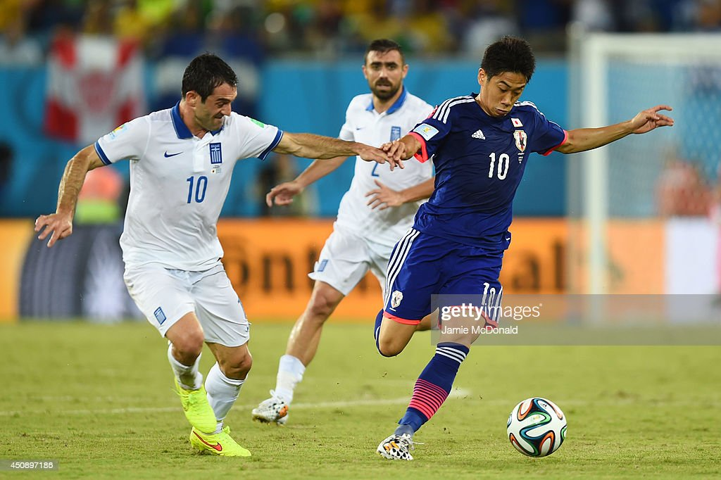 <a gi-track='captionPersonalityLinkClicked' href=/galleries/search?phrase=Shinji+Kagawa&family=editorial&specificpeople=4314029 ng-click='$event.stopPropagation()'>Shinji Kagawa</a> of Japan controls the ball against <a gi-track='captionPersonalityLinkClicked' href=/galleries/search?phrase=Giorgos+Karagounis&family=editorial&specificpeople=240229 ng-click='$event.stopPropagation()'>Giorgos Karagounis</a> of Greece during the 2014 FIFA World Cup Brazil Group C match between Japan and Greece at Estadio das Dunas on June 19, 2014 in Natal, Brazil.