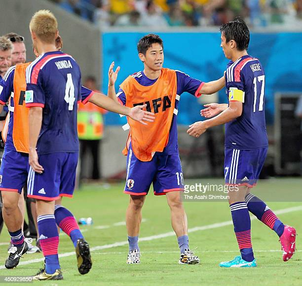 Shinji Kagawa of Japan high fives with Makoto Hasebe at the half time during the 2014 FIFA World Cup Brazil Group C match between Japan and Greece at...
