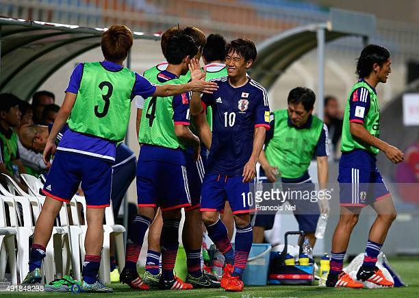 Shinji Kagawa of Japan is congratulated by his teammates during the 2018 FIFA World Cup Asian Group E qualifying match between Syria and Japan at...