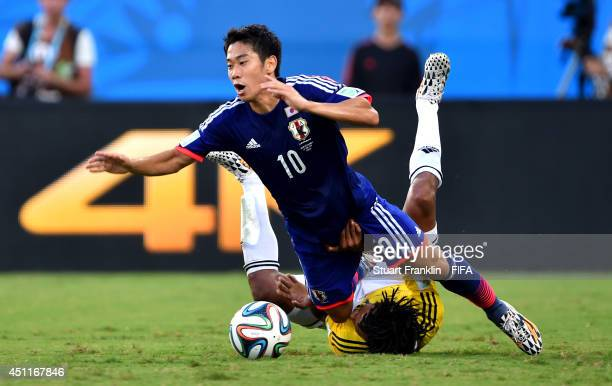 Shinji Kagawa of Japan is tackled by Juan Guillermo Cuadrado of Colombia during the 2014 FIFA World Cup Brazil Group C match between Japan and...