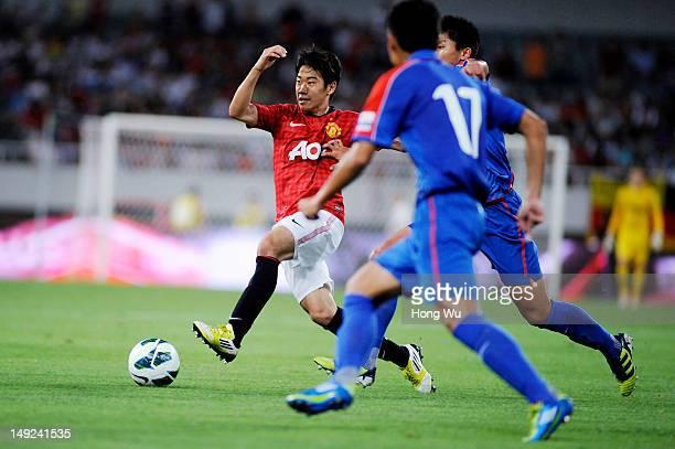 Shinji Kagawa of Manchester United challenges with Fan Lingjiang of Shanghai Shenhua during the Friendly Match between Shanghai Shenhua and...