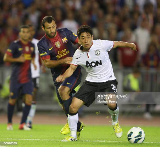 Shinji Kagawa of Manchester United clashes with Javier Mascherano of Barcelona during the preseason friendly match between Manchester United and...