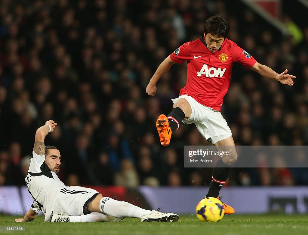 <a gi-track='captionPersonalityLinkClicked' href=/galleries/search?phrase=Shinji+Kagawa&family=editorial&specificpeople=4314029 ng-click='$event.stopPropagation()'>Shinji Kagawa</a> of Manchester United in action with Chico Flores of Swansea City during the Barclays Premier League match between Manchester United and Swansea City at Old Trafford on January 11, 2014 in Manchester, England.