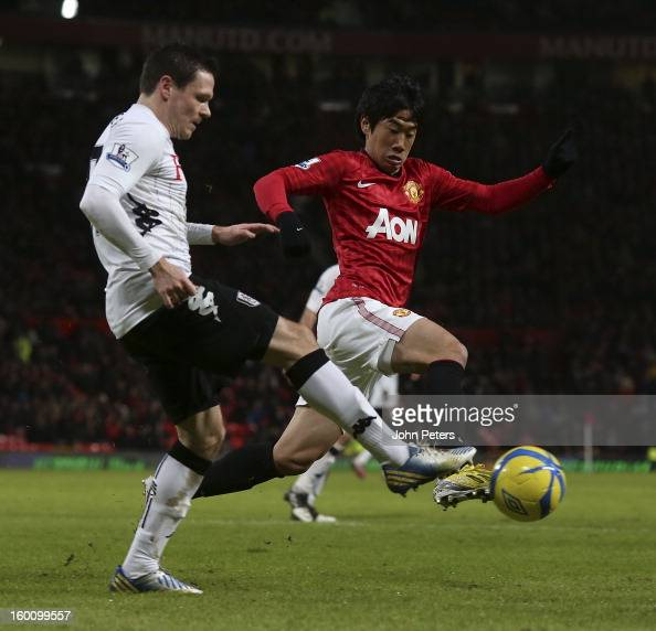 Shinji Kagawa of Manchester United in action with Sascha Riether of Fulham during the FA Cup Fourth Round match between Manchester United and Fulham...