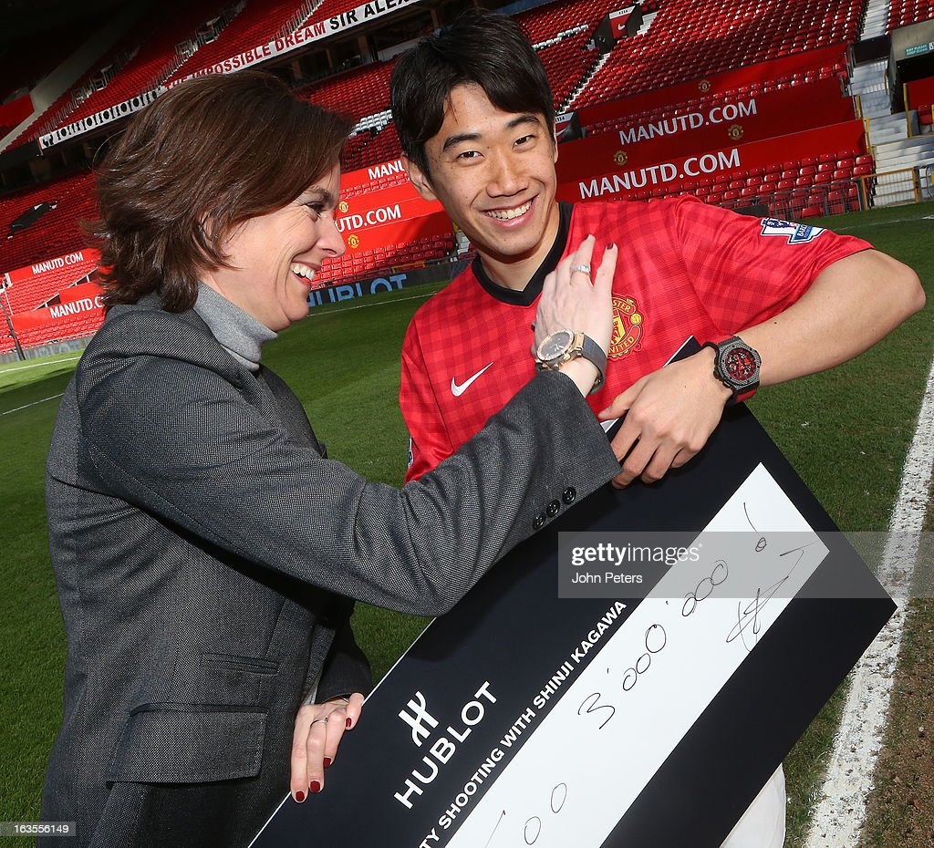 Shinji Kagawa of Manchester United is presented with a cheque for 3,000,000 Japanese Yen by Hublot marketing director Valerie Servageon Grande (L) watches after taking part in a charity shooting event at Old Trafford on March 12, 2013 in Manchester, England.